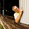 Volunteer Sam Hopper, of Georgetown, works on replacing the support rods for the swine barn windows at the Floyd County 4-H Fairgrounds on Wednesday afternoon in New Albany. The fair opens on July 8 and runs through July 13. Staff photo by Christopher Fryer