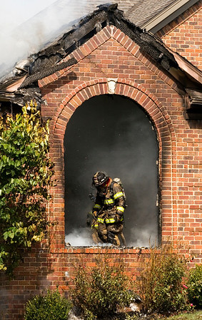 A firefighter works the scene of a house fire at 4009 Cicalla Court in the Jackson Springs development in Greenville on Thursday morning. No one was injured in the fire, which started at about 10 a.m. Staff photo by Christopher Fryer