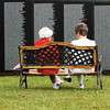 Lillian Miller, left, and Betty Graham sit and talk in front of the Traveling Vietnam Wall in Clarksville. The wall and replicas of the Tomb of the Unknown Soldier and John F. Kennedy grave site are on display, through Sunday, in front of town hall on Veterans Parkway. Staff photo by C.E. Branham