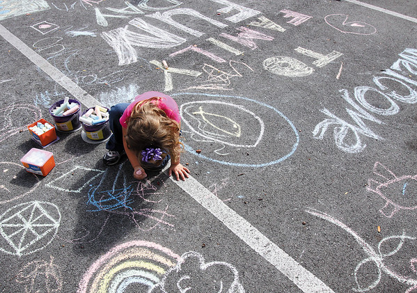 Adelynn Crady draws with chalk at the Clarksville branch of the Jeffersonville Township Public Library Family Fun Day on Saturday. Staff photo by C.E. Branham