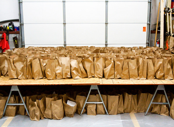 Bags of groceries sit on a make-shift table before being distributed to families at the Salvation Army's Christmas assistance program on Saturday morning in New Albany. Staff photo by Christopher Fryer