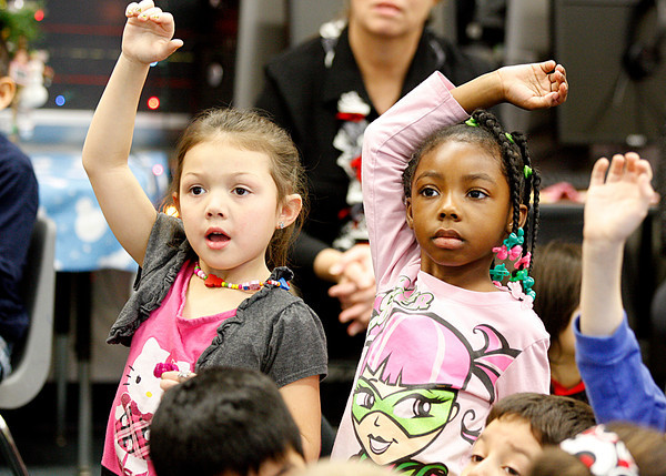 Sarenity Parihus and Shaundrea Molet, kindergarteners at Parkwood Elementary School, raise their hands to ask a question following their virtual field trip to Weather Underground headquarters at the University of Michigan in Ann Arbor, Mich. on Wednesday. Students learned how weather across the country will affect Santa and his reindeer.