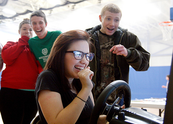 Ryley Biggs, a sophomore at Charlestown High School, and her friends react as she hits a deer during a texting and driving simulator for a Students Against Destructive Decisions event on Friday. Students had a chance to try a simulation involving using a phone while driving or wearing drunk goggles. Staff photo by Jerod Clapp