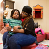 Shantel Ndiaye, Louisville, holds her son Khephra, 3, while he plays a traditional African percussion instrument during the 12th annual Kwanzaa Celebration at the Jeffersonville Township Public Library on Saturday afternoon. Staff photo by Christopher Fryer