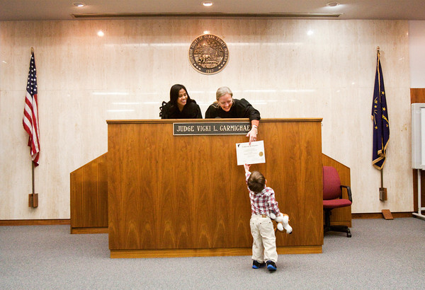 Judge Vicki Carmichael hands Parker Dickerson, 2, Jeffersonville, an adoption certificate for his stuffed animal Puppy Dog during her annual Adopt-A-Doll event in Circuit Courtroom No. 4 at the Clark County Government Building in Jeffersonville on Saturday morning. Staff photo by Christopher Fryer
