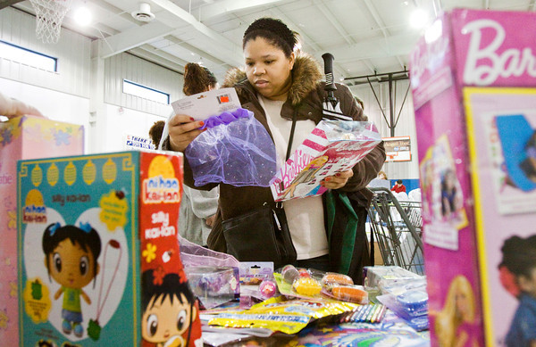 Roshanda Overton, Jeffersonville, picks out toys for her three children at the Salvation Army's Christmas assistance program on Saturday morning in New Albany. Staff photo by Christopher Fryer