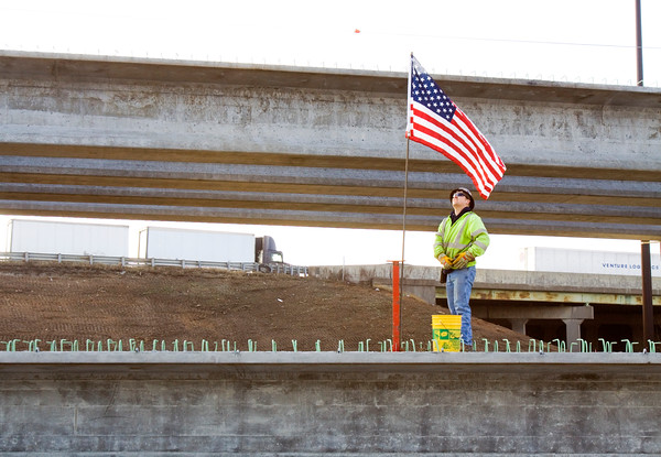 Joe Deck, Vevay, puts up an American flag before setting up a safety cable during a bridge-beam setting for the Ohio River Bridges Project at the corner of Broadway and Sixth streets in Jeffersonville on Monday afternoon. Crews set five 67 ton beams on the site, and they are the first of close to 1,000 beams that will be used in the project. Staff photo by Christopher Fryer