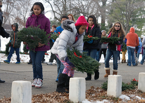Fifth-graders from Hazelwood Middle School lay wreaths at the headstones of soldiers at the New Albany National Cemetery on Friday. Students raised about $2,500 to purchase the wreaths. Staff photo by Jerod Clapp