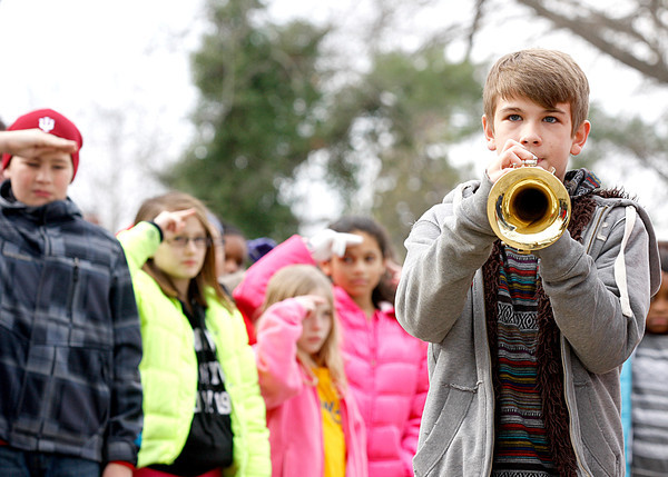 "Nick Teague, a seventh-grader at Hazelwood Middle School, plays ""Taps"" at the end of the school's annual trip to the New Albany National Cemetery on Friday. Students have raised money to place wreaths on graves at the cemetery for the last eight years. Staff photo by Jerod Clapp"