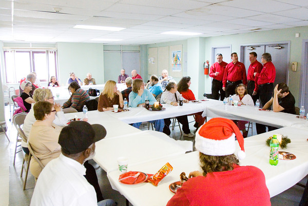 Residents look on as Finish Line, a barbershop quartet with the Thoroughbred Chorus out of Louisville, perform in the dining room at the Clark Arms apartments during the Clark County Housing Authority's holiday party for the residents of the facility in Jeffersonville on Thursday afternoon. Staff photo by Christopher Fryer
