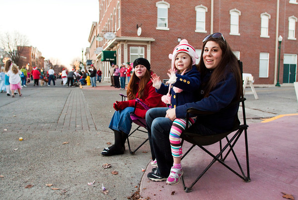 Bailey Atkinson, Jeffersonville, holds her daughter, Aria Hinkle, 3, as they watch the Light Up Holiday Parade move down Spring Street in downtown Jeffersonville on Saturday evening. Staff photo by Christopher Fryer