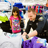 New Albany Police Department patrolman Ryan Durham, Georgetown, helps Addison Ruiz, 7, New Albany, shop for clothes during the Fraternal Order Of Police 99 Lee Deich Memorial Lodge's annual Cops for Kids event at Meijer along Charlestown Road in New Albany on Tuesday evening. Each of the 68 children registered to participate in the event were allotted $250 for clothing, necessities and up to three small toys. Staff photo by Christopher Fryer