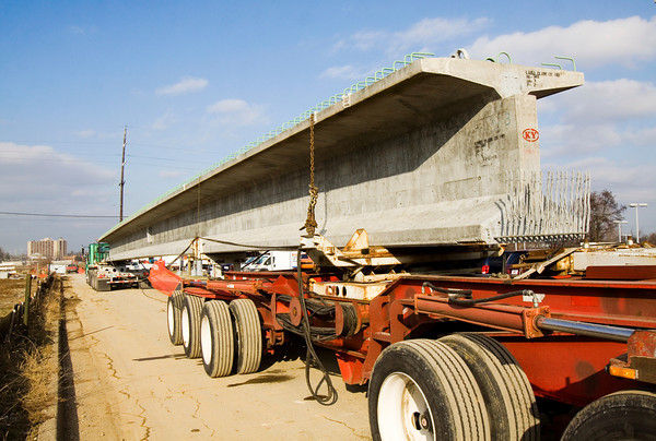 A bridge beam for the Ohio River Bridges Project sits on a semitrailer before being set at the corner of Broadway and Sixth streets in Jeffersonville on Monday afternoon. Crews set five 67 ton beams on the site, and they are the first of close to 1,000 beams that will be used in the project. Staff photo by Christopher Fryer