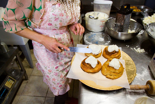 Owner Laura Buckingham spreads icing on bacon cinnamon rolls at her bakery Bread and Breakfast at the corner of Bank and Main streets in downtown New Albany. Staff photo by Christopher Fryer