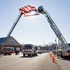 An American flag flies above a Charlestown Volunteer Fire Department engine as it  is driven past the department's headquarters along Park Street while carrying the casket of Carl Glen Hall during a funeral procession to Charlestown Cemetery on Friday afternoon. Hall passed away on December 21 at the age of 67. He was a member of the fire department for 50 years. Staff photo by Christopher Fryer