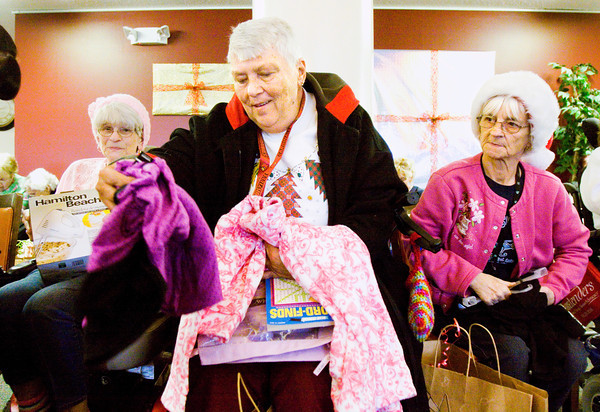 Yellowwood Terrace residents Lynda Jones, middle, Mary Jenkins, left, and Ingeborg Lang open their Christmas gift bags during Home Instead Senior Care's Be a Santa to a Senior gift delivery in Clarksville on Tuesday afternoon. Staff photo by Christopher Fryer