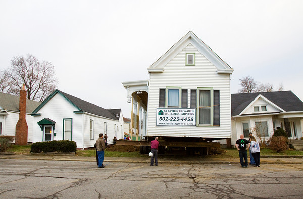 Bystanders look on as a building-moving crew works to position a shotgun-style house on its new lot at 1718 Shelby St. after moving it from 1815 Shelby St. in New Albany on Wednesday afternoon. Staff photo by Christopher Fryer