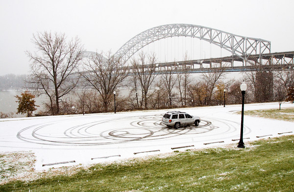 Randall Roberts, New Albany, uses his SUV to do donuts in the snow along the New Albany riverfront on Friday afternoon. Several inches of snow have been forecast to fall from the winter-weather system, and temperatures are expected to remain below freezing on Saturday. Staff photo by Christopher Fryer