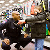 Major Kenny Kavanaugh, of the Jeffersonville Police Department, helps Camden Phillips, 6, Jeffersonville, shop for a new winter coat during the Fraternal Order of Police Lodge No. 100's annual Shopping With A Cop event at Meijer along Allison Lane in Jeffersonville on Monday afternoon. Each of the 19 children from Jeffersonville were allotted about $200-$250 for clothing, shoes, and a few toys. Staff photo by Christopher Fryer