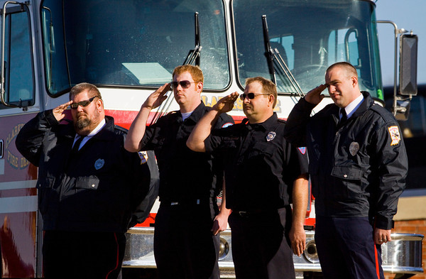 Sellersburg and Clarksville firefighters salute as the funeral procession for Carl Glen Hall moves past the Charlestown Volunteer Fire Department headquarters along Park Street in Charlestown on Friday afternoon. Hall passed away on December 21 at the age of 67. He was a member of the Charlestown Volunteer Fire Department  for 50 years. Staff photo by Christopher Fryer