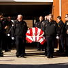Firefighters with the Charlestown Volunteer Fire Department carry the casket of Carl Glen Hall to one of their engines for a funeral procession to Charlestown Cemetery after a service at Grayson Funeral Home on Friday afternoon. Hall passed away on December 21 at the age of 67. He was a member of the fire department for 50 years. Staff photo by Christopher Fryer