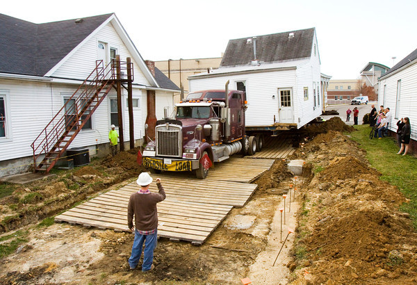 A building-moving crew works to position a shotgun-style house on its new lot at 1718 Shelby St. after moving it from 1815 Shelby St. in New Albany on Wednesday afternoon. Staff photo by Christopher Fryer