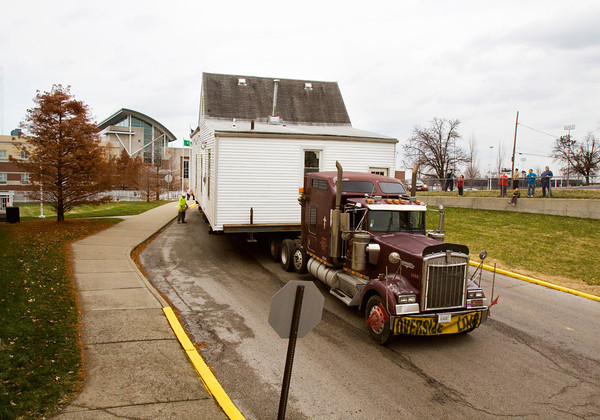 A building-moving crew carries a shotgun-style house through the parking lot of New Albany High School on the way to its new location at 1718 Shelby St. in New Albany on Wednesday afternoon. Staff photo by Christopher Fryer