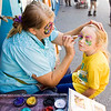 Aleah Byers, 5, Jeffersonville, has a butterfly painted on her face by Brenda Brumett, Crothersville, at Brenda's Creative Face Painting booth during Harvest Homecoming in downtown New Albany on Thursday afternoon. Staff photo by Christopher Fryer