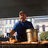 Dave Runyon, Mt. Washington, Ky., coats pork chops while working the grill at the Berts Kitchen booth during Harvest Homecoming in downtown New Albany on Thursday afternoon. Staff photo by Christopher Fryer