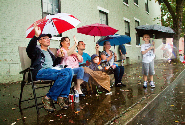 From left, Sam and Pam Dragoo, Aaron and Ellis Smith, and Sarah and Gavin Riley, look on as the Harvest Homecoming Parade moves down Spring Street in New Albany on Saturday afternoon. Staff photo by Christopher Fryer