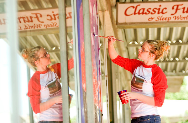 Parkview Middle School student Caroline Elliott, 14, Jeffersonville, works on a Harvest Homecoming window painting with her classmates on the outside of Classic Furniture & Sleep World at the corner of Main and Pearl streets in downtown New Albany on Friday morning. Staff photo by Christopher Fryer