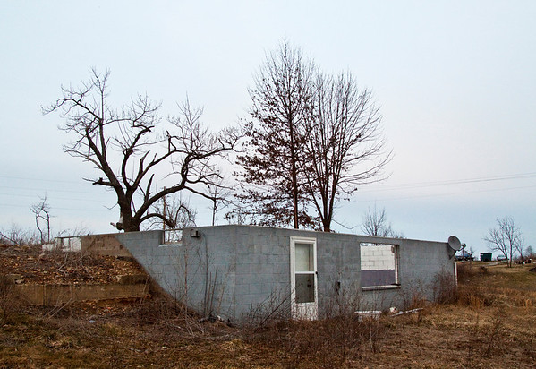 The basement is all that remains of Kristina Jackson's home in Daisy Hill after it took a direct hit during the March 2 tornadoes last year. Donna Kaelin, Jackson's mother, and Will Callahan drove from their New Pekin home to check on family and seek shelter in the basement that day, and Callahan suffered injuries to his back and right leg when the storm hit the house. Staff photo by Christopher Fryer
