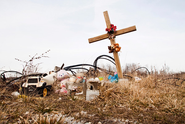 Weathered stuffed animals, burned down candles, a cross, and other mementos serve as a memorial on the lot where the Babcock family used to rent a mobile home in New Pekin. The home was destroyed during the March 2 tornadoes last year and none of the five Babcock family members survived. Staff photo by Christopher Fryer