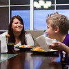 Trish Gilles jokes around with Collin, her youngest child, as they eat dinner in their new home in Henryville on Friday evening. The family lost their original house and suffered severe injuries last year when their home was hit by the March 2 tornadoes. Staff photo by Christopher Fryer