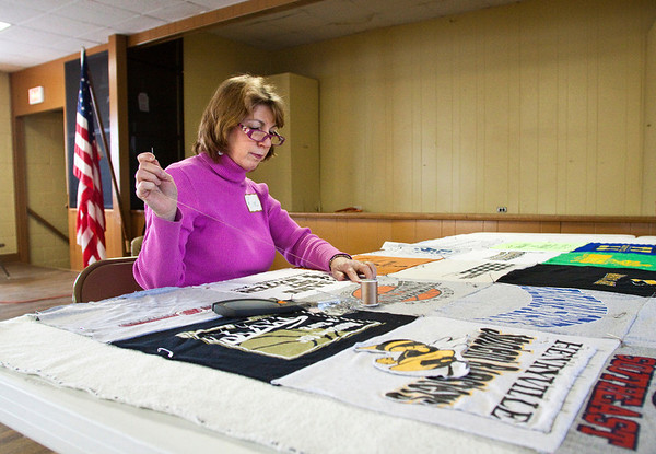 Kim Waller works on a memory quilt, made out of shirts, for the former Henryville High School basketball coach, Perry Hunter, during the Collecting Stories Project in the Henryville Community Center on Saturday afternoon. The project was organized through the March 2 Recovery's Spiritual and Emotional Recovery Team as a way for people affected by the storms to document their stories. Stations at the event included drawing, scrap-booking and journaling. A videography crew was also at the event so people could record their stories. Staff photo by Christopher Fryer