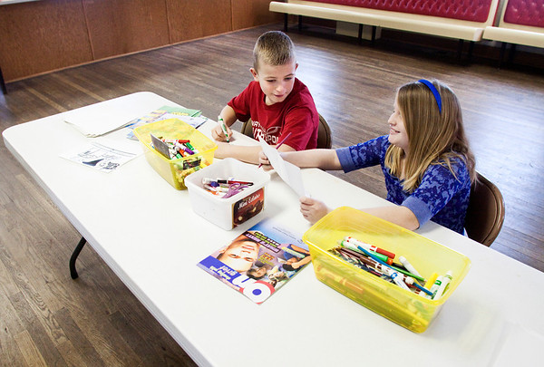 Mia Gilles and her cousin Samuel Gilles work at the drawing station during the Collecting Stories Project in the Henryville Community Center on Saturday afternoon. The project was organized through the March 2 Recovery's Spiritual and Emotional Recovery Team as a way for people affected by the storms to document their stories. The stations included drawing, scrap-booking and journaling. A videography crew was also at the event so people could record their stories. Staff photo by Christopher Fryer