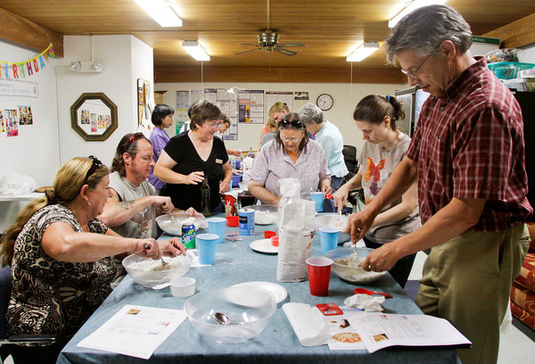 Instructor Peggy Roberson, center left, helps participants as they make pizza dough during a Food For Thought Cookbook Group workshop in the staff lounge at the New Albany-Floyd County Public Library on Wednesday evening in New Albany. About a dozen participants used six ingredients to create a quick rise, yeast dough from scratch. Staff photo by Christopher Fryer