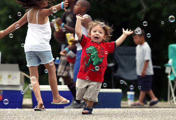 Antonio Patilan runs through bubbles Saturday afternoon at the Cross Creek Apartments youth fun day in New Albany. Staff photo by C.E. Branham