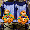 Three-month-old twins Jalonnie, right, and Jarizzmah Taylor, New Albany, sit in their pumpkin costumes during the costume contest at the 27th annual Costume Carnival in Newlin Hall at the Floyd County 4-H Fairgrounds on Thursday evening. The twins placed first in the infant to one-year-old round of the contest. About 50 businesses and organizations were also at the event with trick-or-treat and game stations set up in the hall. Staff photo by Christopher Fryer