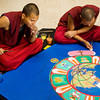 Tibetan monks Dawa, left, and Tenpa work to complete a World Peace sand mandala at the Carnegie Center in New Albany on Thursday afternoon. Seven monks from the Labrang Tashi Kyil Monastery in Dehradun, India worked on the project that took days to complete. Staff photo by Christopher Fryer