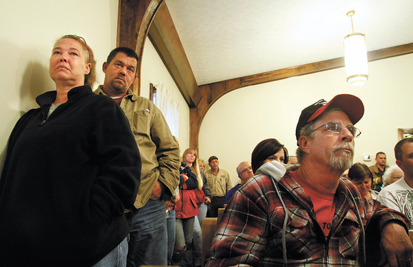 From left, Joanie and Tom Fanning and Jeff Hurst, all of Daisy Hill, listen to authorities discuss issues concerning the tornado recovery effort in their area during a community meeting at the Daisy Hill United Methodist Church Thursday afternoon. Staff photo by Christopher Fryer