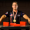 Mike West leans on an arm wrestling table at his Floyds Knobs home last Wednesday. West competed in the World Armwrestling Federation Championship in Poland earlier this month, and came home with his fourth world title. Staff photo by Christopher Fryer