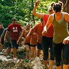 Racers try to keep their balance while negotiating an obstacle during the Muddy Fanatic 5K Adventure Race at the former Glenwood Training Center in Sellersburg on Saturday morning. Over 2000 participants negotiated over 30 obstacles on a 3.1 mile course either as individual racers or as part of a team. Staff photo by Christopher Fryer