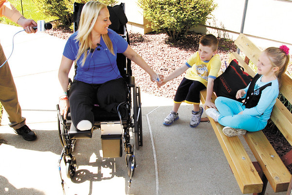 Stephanie Decker holds hands with her son Dominic, 8, while her daughter Reese, 5 looks on as they take questions from the media after her release from Southern Indiana Rehab Hospital in New Albany on Monday afternoon. Both of Decker's legs had to be partially amputated after she was injured by debris while protecting her children in the basement of their home when the March 2 tornadoes hit the Henryville area. Staff photo by Christopher Fryer