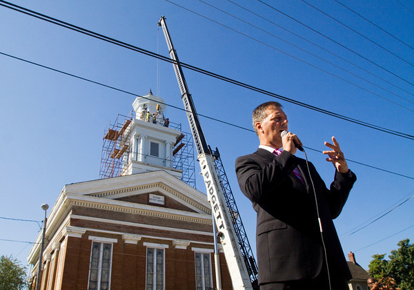 Jerry Finn, of the group Friends of the Town Clock Church and the executive director of the Horseshoe Foundation of Floyd County, speaks while a crew with DM Masonry works to place one of the four restored clock faces back on the clock tower of the Second Baptist Church during a ceremony at the historic site in downtown New Albany on Tuesday morning. Staff photo by Christopher Fryer