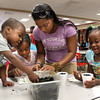 Derrick Brown, left, Celeste Brown, Kaila Brown, and their mother Christina Brown plant flower and okra seeds at the Jeffersonville-Metro Parents in Education Group Back to School Jam 2012 Friday evening. The ninth-annual event, held at Jeffersonville High School, provided students and parents with school supplies, snacks, sustainability resources and educational information. Staff photo by C.E. Branham