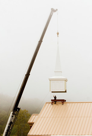 Nolan Carter, of Munns Manufacturing, helps to guide the steeple into place on the roof of the new Wesley Chapel United Methodist Church in Floyds Knobs on Friday morning. The 2500 pound steeple is one of the last exterior elements to be added to the new church, which plans to hold its first service on Easter of next year. Staff photo by Christopher Fryer