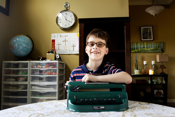 Ian Receveur, 7, leans on his brailler at his family's home in Georgetown on Wednesday afternoon. Receveur was born with X-linked juvenile retinoschisis, a genetic eye disease that caused him to go blind. He will be competing in the Braille Challenge at the Braille Institute in Los Angles on Saturday. Staff photo by Christopher Fryer