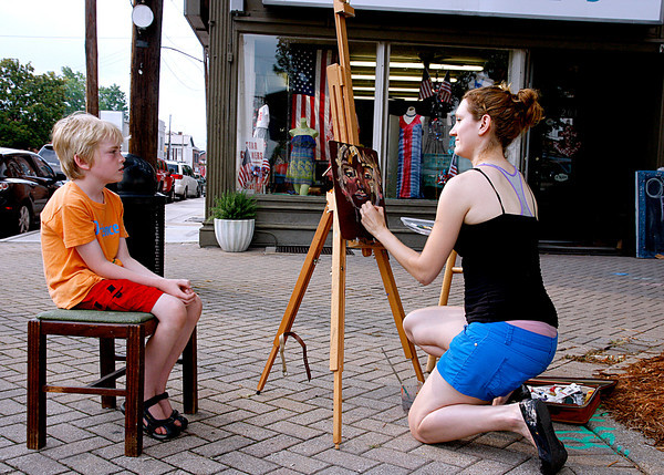 Carson Borchers gets his portrait painted by Sarah LaBarge during the New Albany Public Art Walk. Participants had chances to see new art and create their own at and around each installation. Staff photo by Jerod Clapp