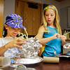 Blake Barrett, 8, and his sister Ashlynn, 10, both of Sellersburg, use tinfoil, pie pans, and other household items to construct interplanetary-space rovers during the Space Explorers summer program at the New Albany-Floyd County Public Library on Thursday afternoon. Around 30 third, fourth and fifth graders were signed up to participate in the craft project. Staff photo by Christopher Fryer